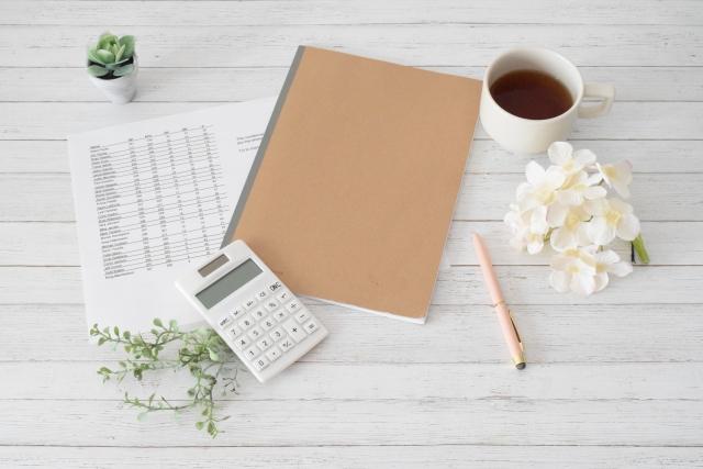 電卓とノート、コーヒー