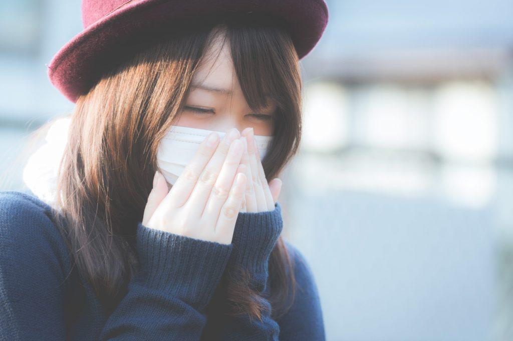 花粉症でくしゃみをするマスク姿の女性