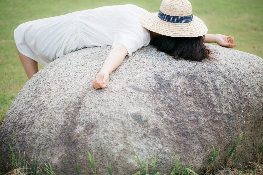 石の上で寝る女性