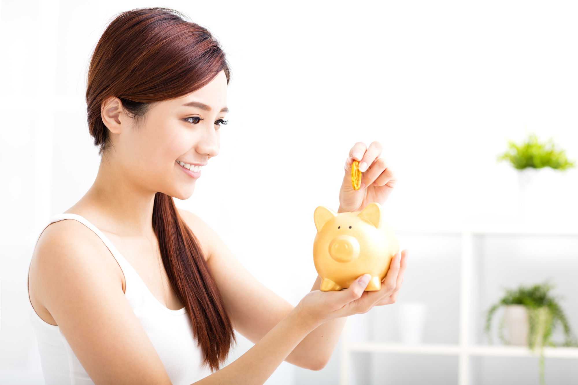 Happy young woman saving money in the piggy bank