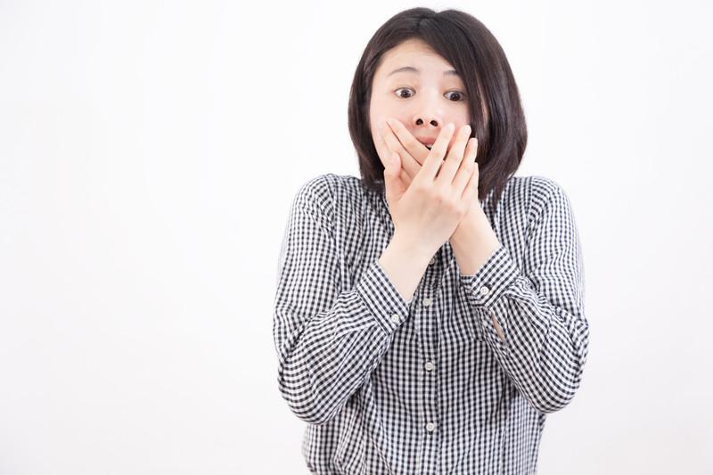 驚いて口を隠す女性